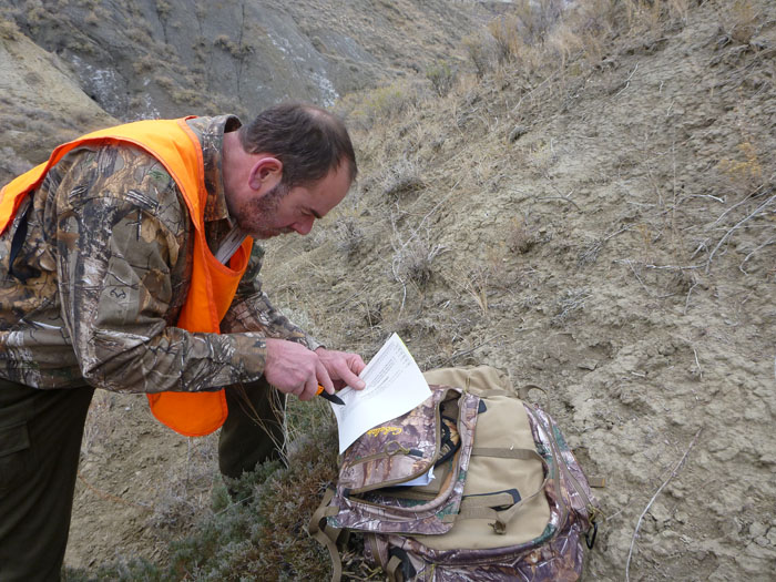Jim Heins cutting his Montana deer tag - photo by Rob Endsley